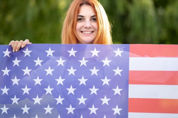 Счастливая молодая рыжеволосая женщина позирует с национальным флагом сша, стоя на открытом воздухе в летнем парке. Premium Фотографии