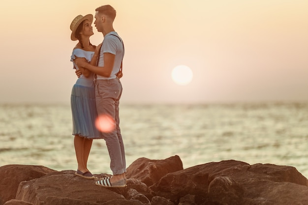 Happy young romantic couple relaxing on the beach and watching the sunset Free Photo