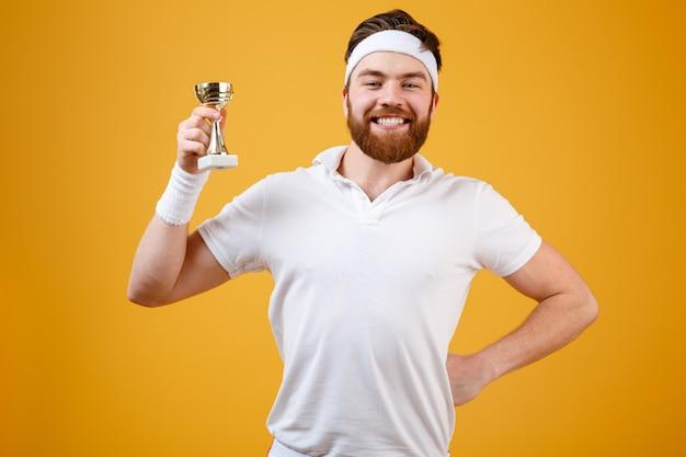 報酬を保持している幸せな若いスポーツマン 無料写真