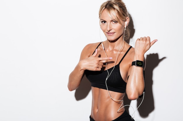 Happy young sportswoman in earphones pointing Free Photo