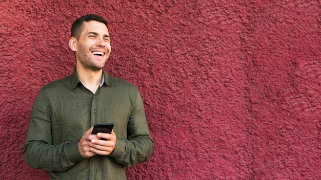 Happy young stubble man holding cellphone standing near rough wall Free Photo