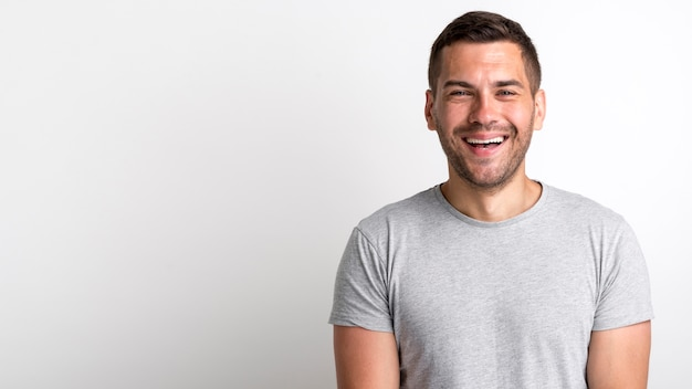 Happy young stubble man laughing and standing over white backdrop Premium Photo