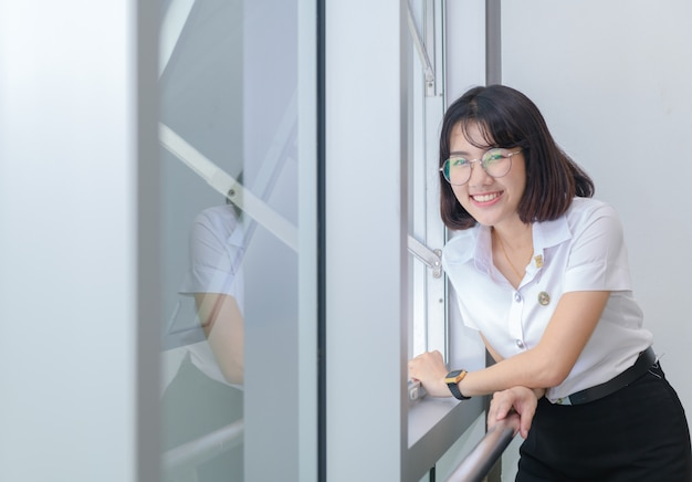 Happy young students in uniform smile near window, education concept Premium Photo