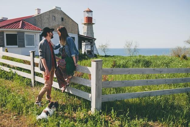 Счастливая молодая стильная хипстерская пара в любви, гуляющая с собакой в сельской местности, летняя мода в стиле бохо Бесплатные Фотографии