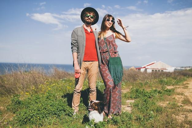 Счастливая молодая стильная хипстерская влюбленная пара гуляет с собакой в сельской местности Бесплатные Фотографии