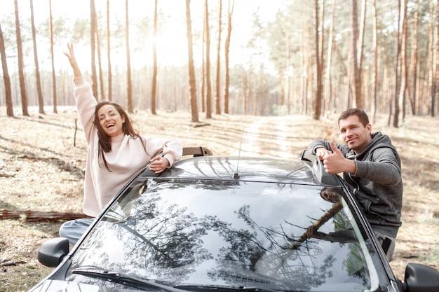 幸せな若い女と男が車の窓から登った。森の中を車で旅行。カントリートリップ。車での休暇 Premium写真