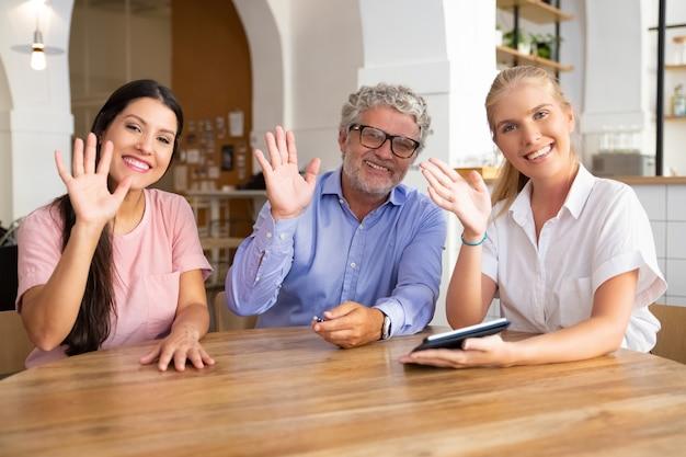幸せな若い女性と成熟した男性は、タブレットで女性の専門家とテーブルに座って、カメラを見て、ポーズをとって、笑顔で手を振ってこんにちは 無料写真