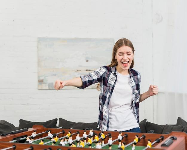 Счастливая молодая женщина, аплодисменты во время игры в настольный футбол дома Бесплатные Фотографии