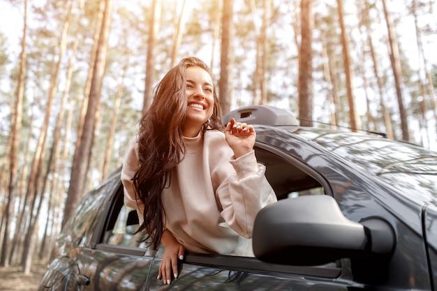 幸せな若い女が車の窓から登った。森の中を車で旅行。カントリートリップ。車での休暇 Premium写真