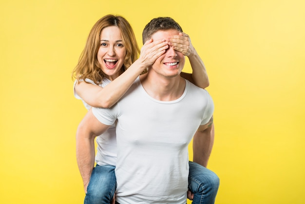 Happy young woman covering eyes while riding boyfriend's back against yellow backdrop Free Photo