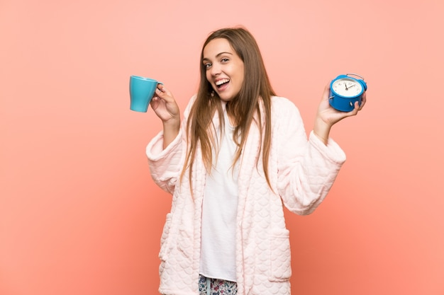 Happy young woman in dressing gown over pink wall holding a cup of coffee Premium Photo