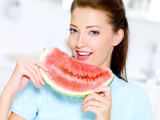 Счастливая молодая женщина ест красный арбуз Бесплатные Фотографии