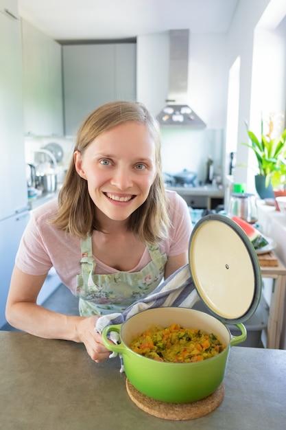 彼女のキッチンで料理を楽しんで、野菜の食事で鍋を開き、テーブルにもたれて、カメラに笑顔幸せな若い女。垂直ショット。フードブロガーのコンセプト 無料写真