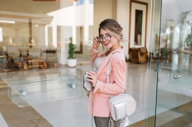 Happy young woman entering glass door into modern hotel, cafe, business centre. wearing stylish glasses, pink jacket, little silver backpack. Free Photo