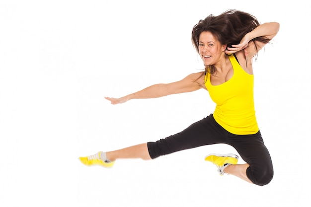 Happy young woman in fitness wear jumps Free Photo
