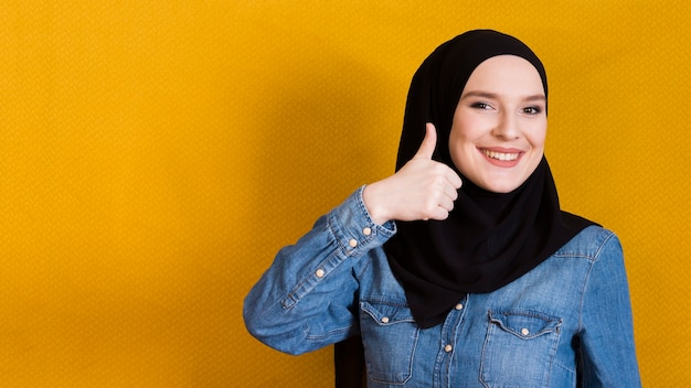 明るい黄色の表面に対して幸せな若い女ジェスチャーサムアップ Premium写真