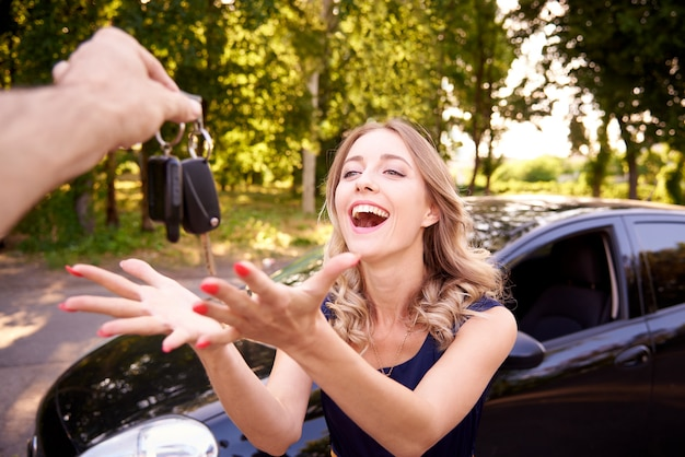 Happy young woman gets the keys to the car. Premium Photo