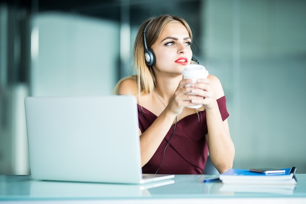 Felice giovane donna in cuffie nel call center e bere il caffè in ufficio. Foto Gratuite