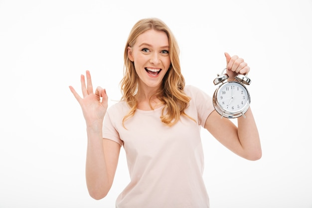 Happy young woman holding alarm clock showing ok gesture. Free Photo