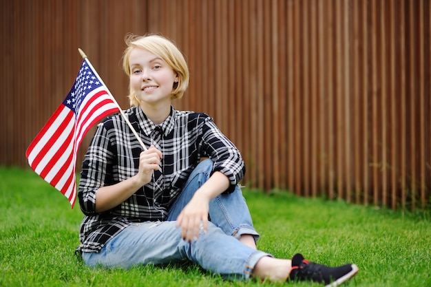 Happy young woman holding american flag. independence day concept. Premium Photo