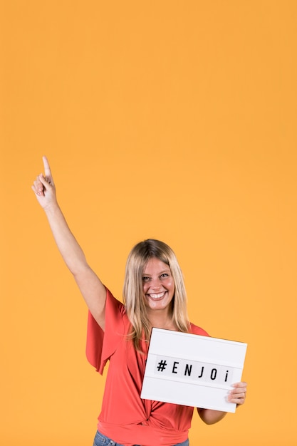 Happy young woman holding enjoy text light box with arm raised in front of yellow backdrop Free Photo