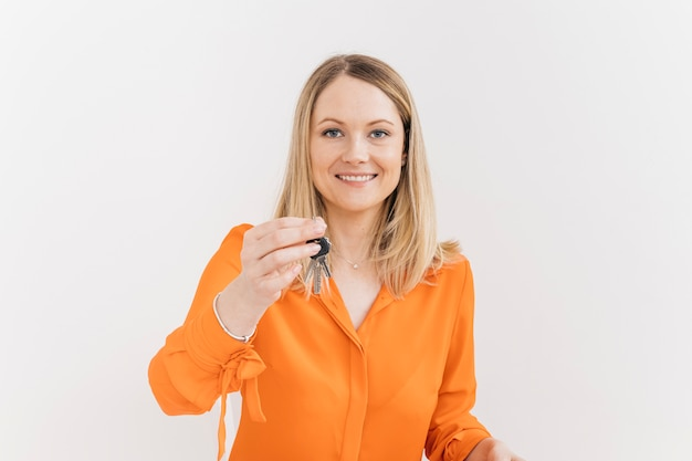 Happy young woman holding keys against white wall Free Photo