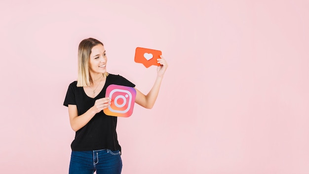Happy young woman holding love and instagram icon Free Photo