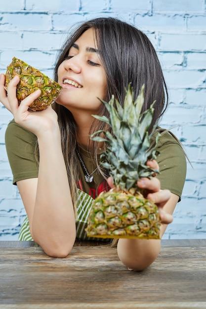 파란 표면에 파인애플을 들고 행복 한 젊은 여자 무료 사진