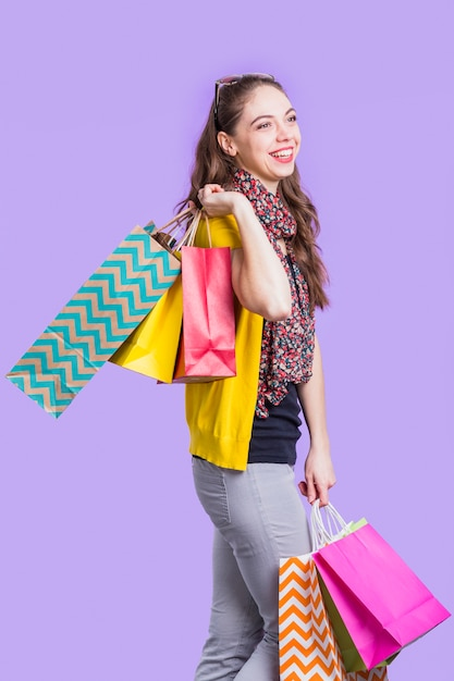 Happy young woman holding shopping bags standing against lavender surface Free Photo
