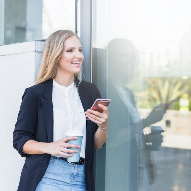 幸せな若い女性は携帯電話を使用してコーヒーカップを取る 無料写真