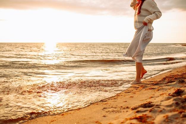 夕日の海岸で空の砂浜を一人で歩いて、彼女の足で水に触れるドレスを着た幸せな若い女。 freedoom、休暇 Premium写真
