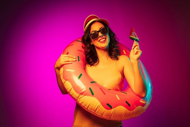 トレンディなピンクのネオンにキャンディーとゴム製のビーチリング、赤いキャップとサングラスで幸せな若い女性 無料写真