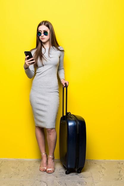 スーツケースとチケットでパスポートを運ぶサングラスで幸せな若い女は黄色の壁に携帯電話を使用してください。 無料写真