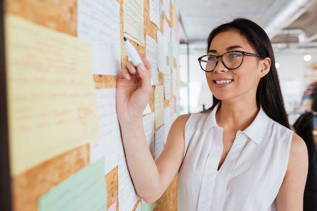 Счастливая молодая женщина в очках, написание рекламы на доске объявлений Premium Фотографии