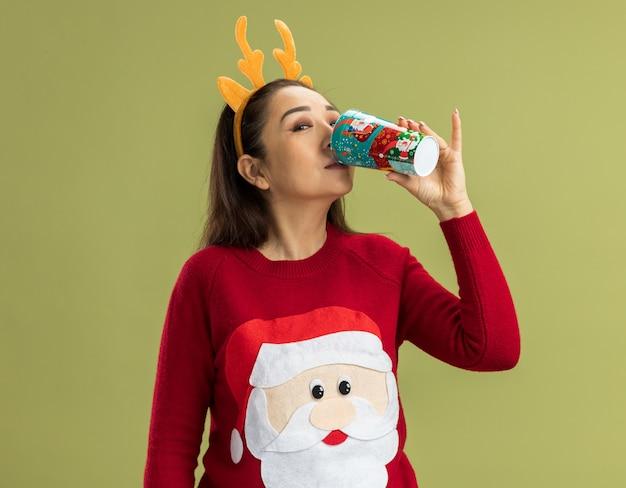 다채로운 종이 모자에서 마시는 사슴 뿔과 함께 재미있는 테두리를 입고 빨간 크리스마스 스웨터에 행복 한 젊은 여자 무료 사진