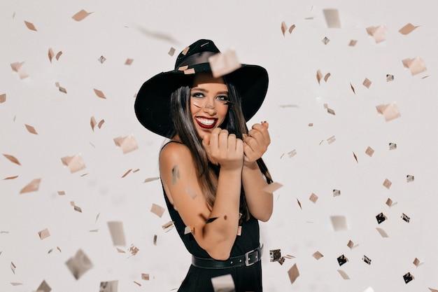 Счастливая молодая женщина в костюме хеллоуина ведьмы с шляпой и черным платьем стоя и усмехаясь над белой стеной с конфетти. halloween party Бесплатные Фотографии