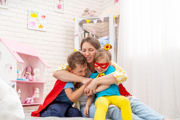 Happy young woman is playing with her children as superheroes hugs them Premium Photo