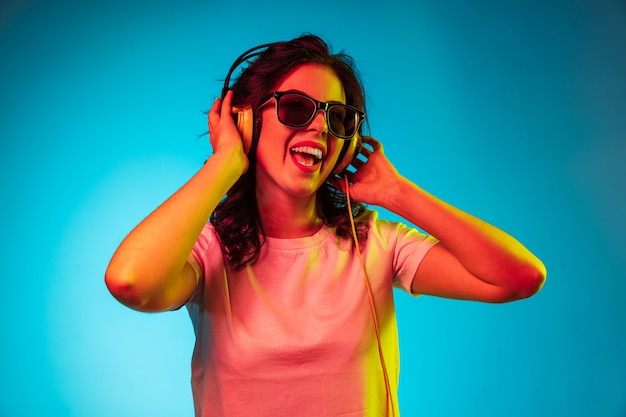 Happy young woman listening to the music and smiling over trendy blue neon studio Free Photo
