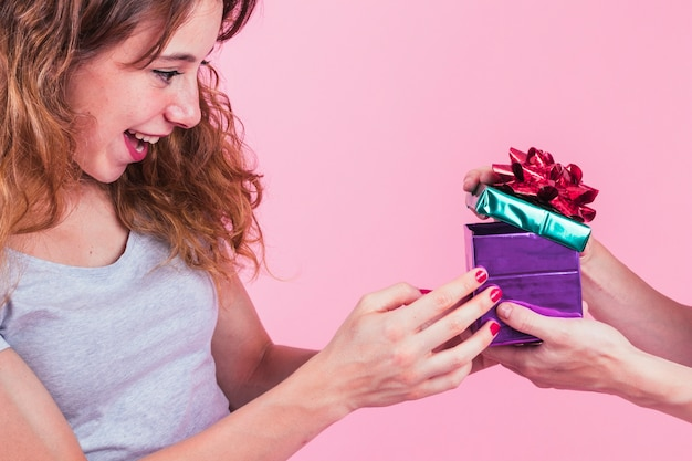 Happy young woman looking at open gift box hold by her friend against pink background Free Photo