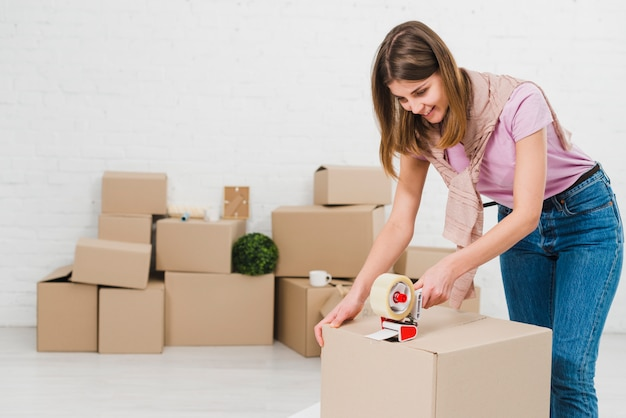 Happy young woman packing cardboard boxes using tape dispenser Free Photo