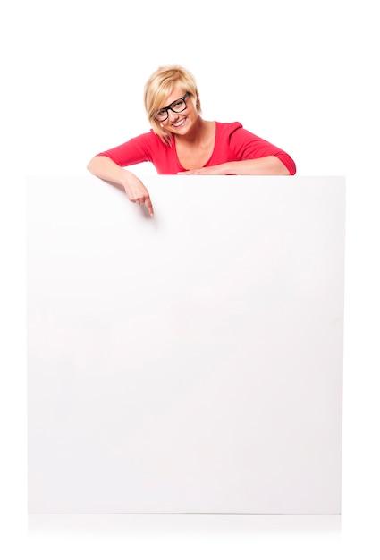 Felice giovane donna che punta al tabellone per le affissioni Foto Gratuite