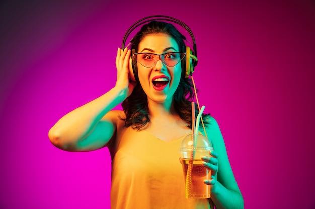 Felice giovane donna in occhiali da sole rossi che beve e ascolta musica al neon rosa alla moda Foto Gratuite