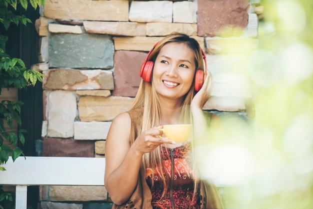La giovane donna felice si rilassa con ascolta la musica favorita al caffè Foto Gratuite