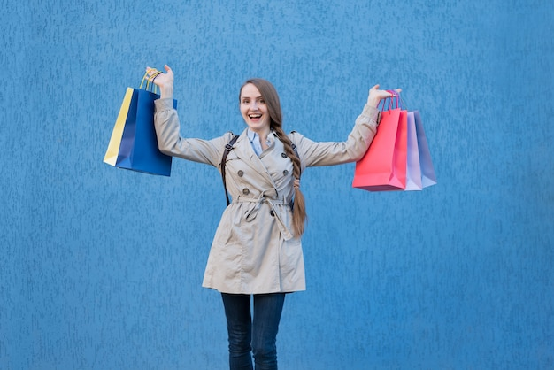 Happy young woman shopaholic with colorful bags. blue street wall on surface Premium Photo