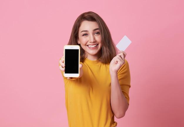 Счастливая молодая женщина, показывая на пустой экран мобильного телефона и кредитной карты, изолированных на розовый. Premium Фотографии
