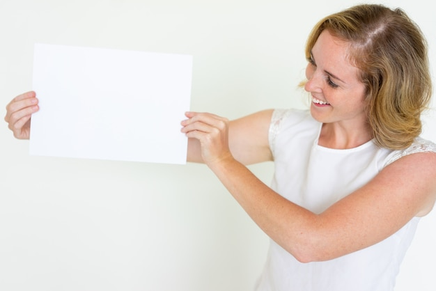 Happy young woman showing blank sheet of paper Free Photo