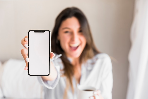 Happy young woman showing white screen mobile phone Free Photo
