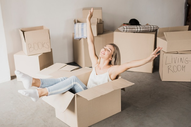 Happy young woman sitting in carton box Free Photo