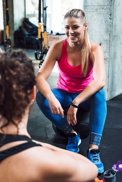 Happy young woman sitting near her friend in gym Free Photo