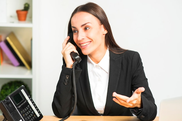Happy young woman sitting in the office talking on telephone gesturing Free Photo